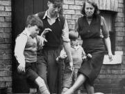 1953年,查尔顿和母亲以及弟弟在家门外踢球。